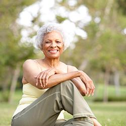Overgangsklachten - vitale vrouw van middelbare leeftijd zit in het gras